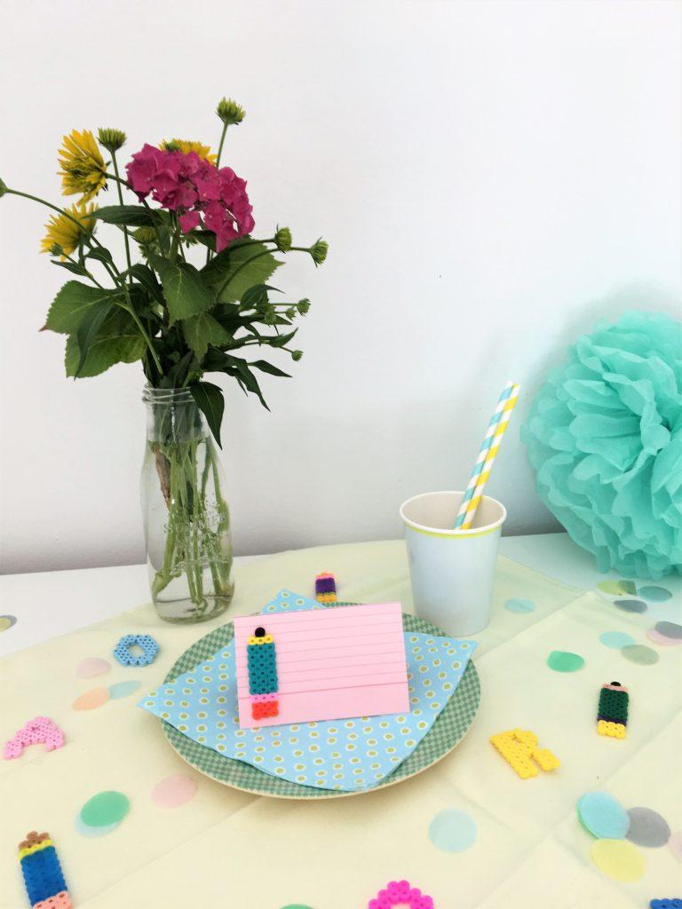 Rosa Tischkärtchen mit Blumen und Tischkonfetti für die Einschulungsfeier