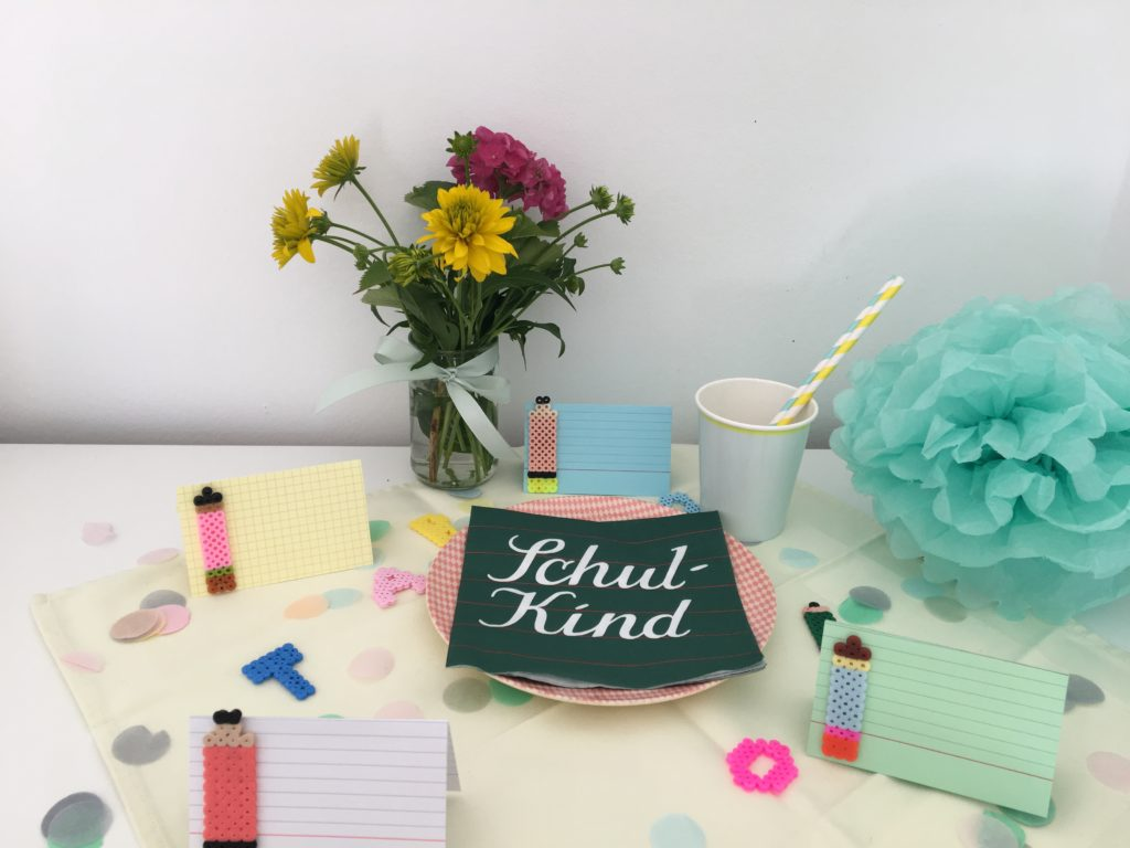 Tischkarten aus Bügelperlen und Karteikarten mit Serviette Schulkind für die Einschulungsfeier